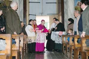 À l'entrée de l'église: bénédiction des fidèles et du clergé